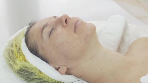 Woman face with closed eyes in beauty saloon with problem aged skin. Acne.