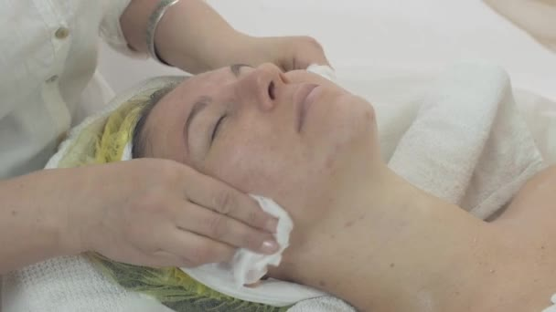 Cosmetologist wipe off woman face by napkin after cosmetic mask in beauty saloon