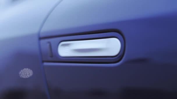 Pohled na bílou ruku na dveře tmavě modré nové auto. Prezentace. Zobrazeno. Automobilu. Studené odstíny