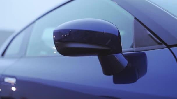Pohled na předních zrcátek nové tmavě modré auto. Prezentace. Zobrazení modelu. Automobilu. Studené odstíny