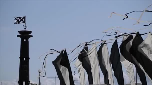 Černé a bílé vlajky s pásky se houpat na vítr v letním dni. Modrá obloha. Sloupec s příznakem