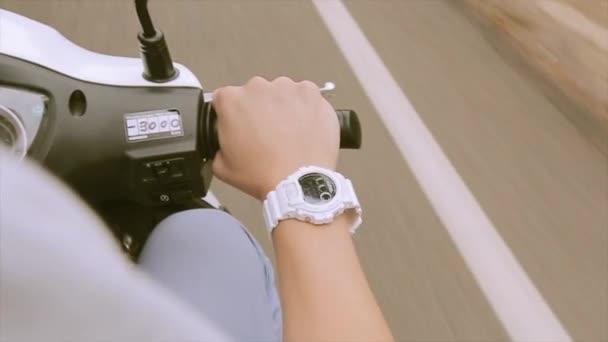 Pohled po ruce muže na motorce jednotky kormidelního kola. Na cestách. Bílé hodinky. Cesta. Cesta
