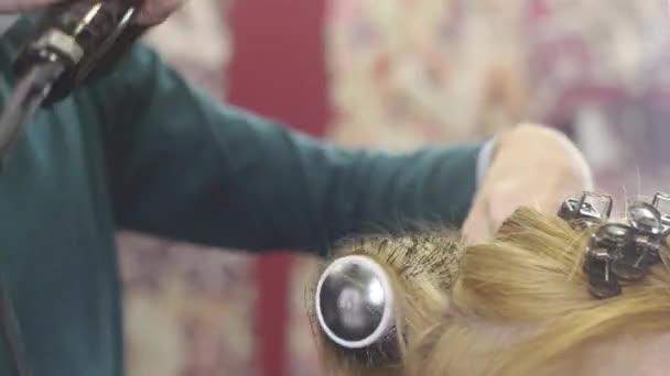Barber zvýšit kořínky vlasů na blond girl hřeben a vysoušeč vlasů v salonu krásy. Vytváření účesu