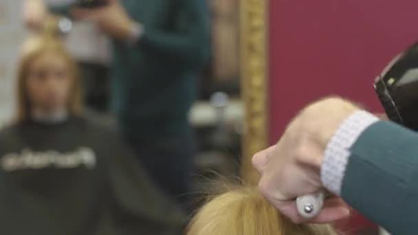 Kadeřnictví styl horní části vlasů na blond girl hřeben a vysoušeč vlasů v salonu krásy. Objem tvorby