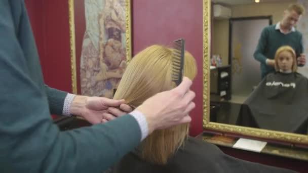 Profesionální kadeřnická hřeben suché vlasy na blond girl od přímé hřeben v salonu krásy. Zrcadlo