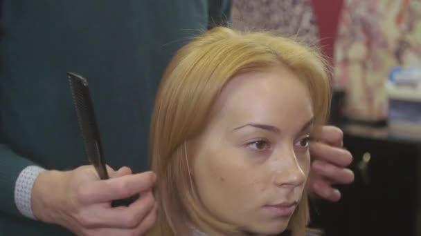 Profesionální kadeřník učešte vlasy Girl od přímé hřeben v salonu krásy. Objem účesu