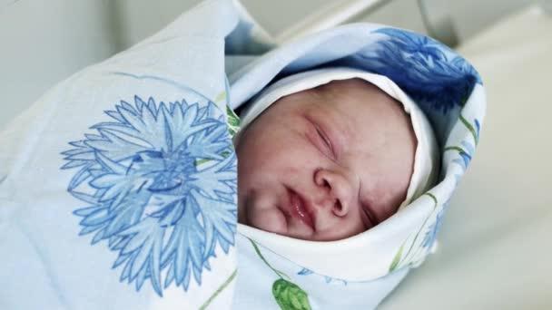 Swaddled újszülött kancsal a nappal, szülészet, kék takarót feküdt. Gyermek