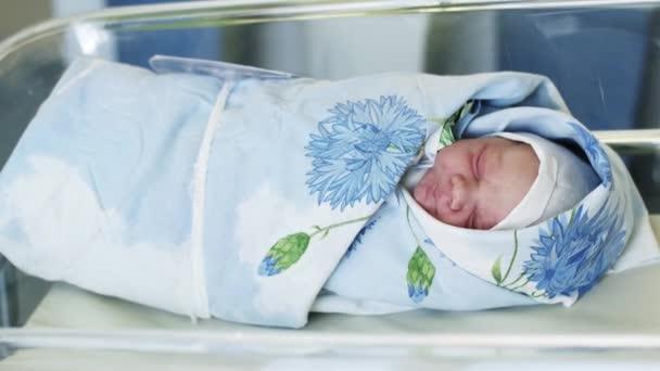 Swaddled a kék takarót újszülött csecsemő feküdt szülőotthon, átlátszó dobozban. Újszülött gyermek