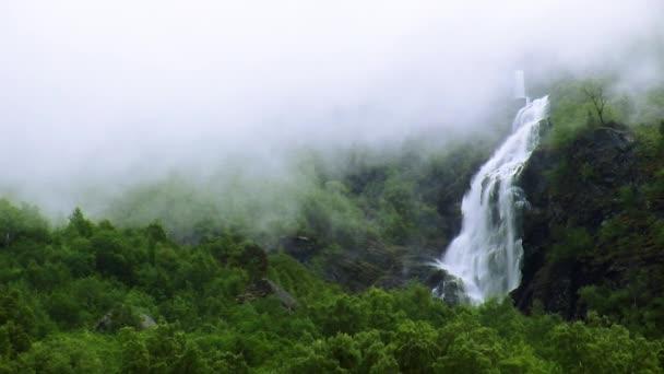 Pohled na vodopád cascade v zeleném lese mezi horami. Letní den. Mlha. Příroda. Nikdo. Zeleň