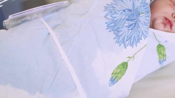 Újszülött kancsal a nappal, smack ajkak rejlik szülőotthon, pelenka, kék takaró.