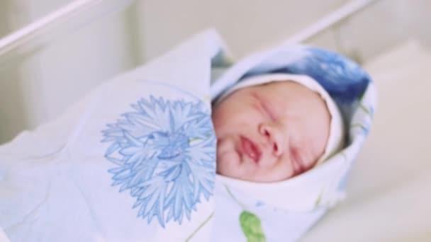 Újszülött baba pofon a szája, hullám szülőotthon, pelenka, kék takarót fej rejlik. Gyermek.