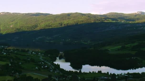 Panoramatický výhled na město v pohoří pokryté zelené lesy letní slunečný den. Západ slunce. Řeka. Příroda