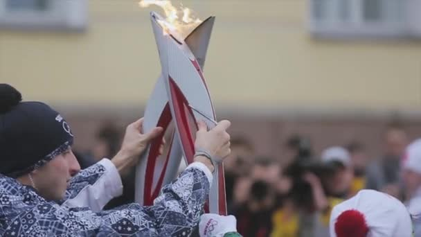 SAINT PETERSBURG, RUSSIA - OCTOBER 27, 2013: Relay race Sochi Olympic torch in Saint Petersburg. Two burning torch together. Moment of pass flame