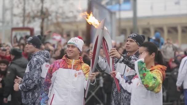 SAINT PETERSBURG, RUSSIA - OCTOBER 27, 2013: Relay race Olympic flame in Saint Petersburg in October. Kandelaki pass flame Kerzhakov. Wave hands