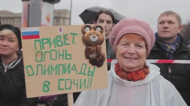 Petrohrad, Rusko - 27 října 2013: Bývalý žena drží plakát s Olympic medvěd. Štafetový závod Soči olympijský oheň v Petrohradu