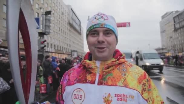 Petrohrad, Rusko - 27 října 2013: štafeta olympijského ohně v Petrohradu. Mužské světlonoš dát rozhovor. Lidé. Automobily