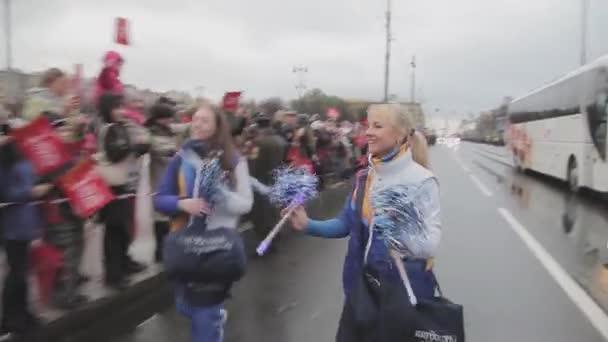Petrohrad, Rusko - 27 října 2013: Dívky v uniformě rozdávat střapce na publikum. Štafetový závod Soči olympijský oheň v Petrohradu