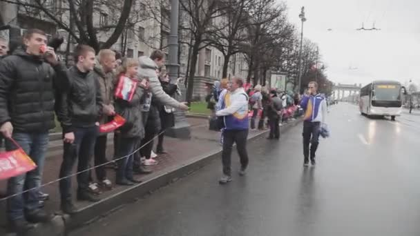 SAINT PETERSBURG, RUSSIA - OCTOBER 27, 2013: Running man in uniform give pompons to people. Relay race of Sochi Olympic flame in Saint Petersburg