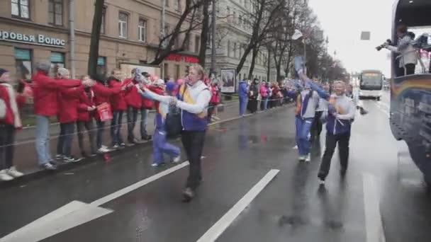 SAINT PETERSBURG, RUSSIA - OCTOBER 27, 2013: Walking people, youth wave pompons, jump. Relay race of Sochi Olympic flame in Saint Petersburg