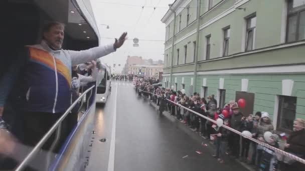 Petrohrad, Rusko-27. října 2013: dospělý muž, vlna pom pom v jízdě autobusem. Retranslační závod Sochi olympijského ohně v Petrohradu. Dívky
