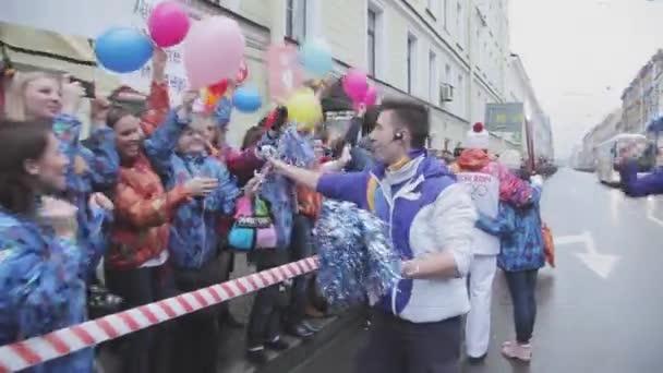 Petrohrad, Rusko-27. října 2013: dobrovolník se na lidi vyruč. V Petrohradě se rozjížďka olympijského ohně Sochi.