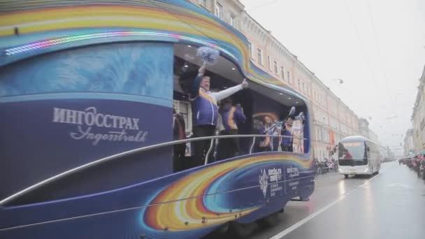 Petrohrad, Rusko-27. října 2013: autobus s dobrovolníky, mávaje povol, tanec. V Petrohradě se rozjížďka olympijského ohně Sochi.
