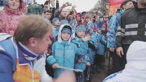 Petrohrad, Rusko - 27 října 2013: štafeta Soči olympijský oheň v Petrohradu. Dospělý muž v uniformě s dětmi vlna pom pom