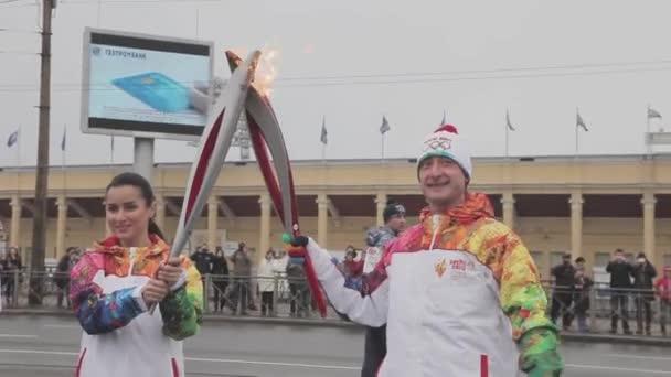 Petrohrad, Rusko - 27 října 2013: štafeta Soči olympijské pochodně v Petrohradu. Pljuščenko předat plamen Kandelaki. Vlna ruce