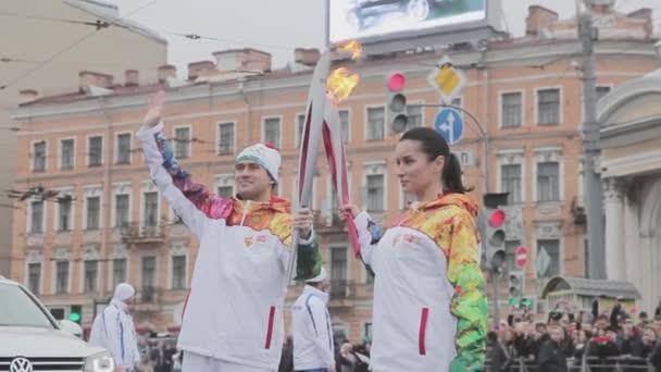 Petrohrad, Rusko - 27 října 2013: štafeta Soči olympijské pochodně v Petrohradu. Kandelaki plamen předat Kerzhakov. Vlna ruce.