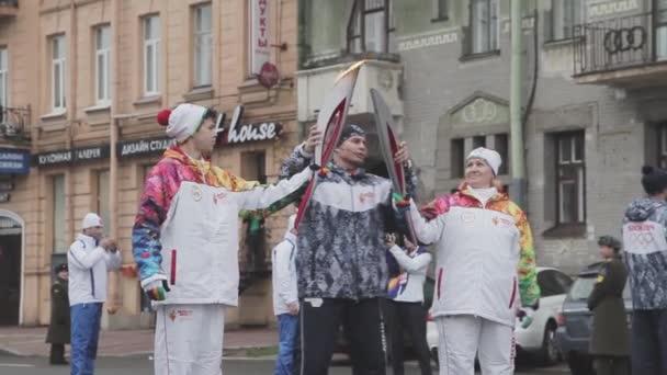 Petrohrad, Rusko - 27 října 2013: štafeta Soči olympijské pochodně v Petrohradu. Světlonoš průchodu plamen do druhého. Vlna ruce