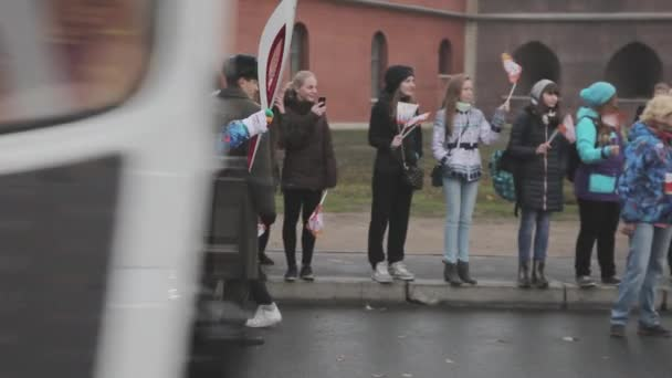 Petrohrad, Rusko - 27 října 2013: štafeta Soči olympijské pochodně v Petrohradu. Světlonoš dostávají plamen. Dav. Průvod