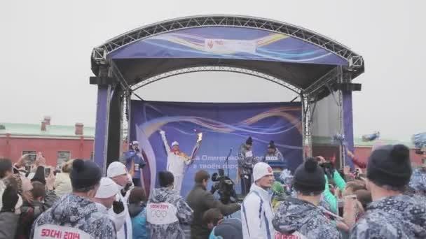 Petrohrad, Rusko - 27 října 2013: štafeta Soči olympijské pochodně v Petrohradu. Světlonoš na jevišti s plamenem. Vlna ruce