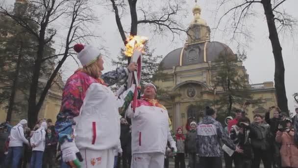 Petrohrad, Rusko - 27 října 2013: štafeta Soči olympijské pochodně v Petrohradu. Světlonoš průchodu plamen. Mávnout rukou. Úsměv