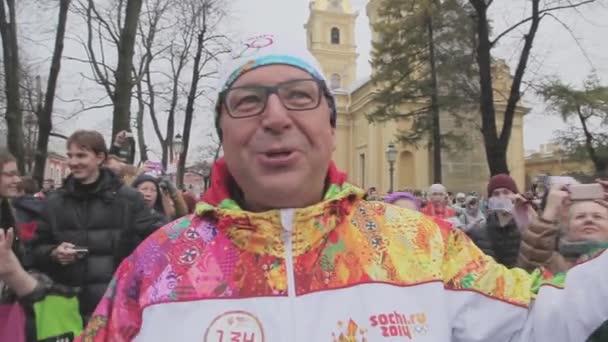 Petrohrad, Rusko - 27 října 2013: štafeta Soči olympijské pochodně v Petrohradu. Světlonoš dát rozhovor v kameře. Petra a Pavla pevnosti