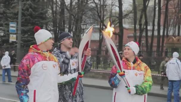 Petrohrad, Rusko - 27 října 2013: štafeta Soči olympijské pochodně v Petrohradu. Ženské světlonoš předat plamen člověka. Vlna ruce