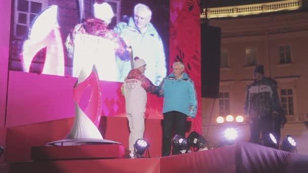 Petrohrad, Rusko - 27 října 2013: Egorova a Poltavchenko Zapal Soči olympijské misku na jevišti v Petrohradu. Palácové náměstí
