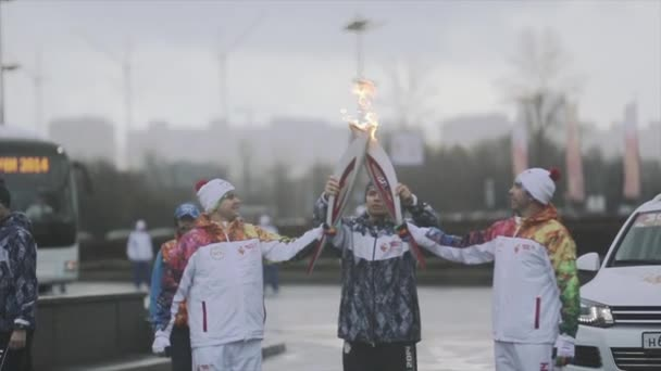 Petrohrad, Rusko - 27 října 2013: štafeta Soči olympijské pochodně v Petrohradu. Mužské světlonoš průchodu plamen. Mávnout rukou. Veselé