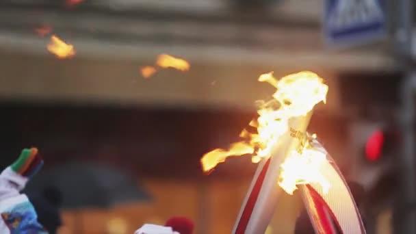 Petrohrad, Rusko - 27 října 2013: štafeta Soči olympijské pochodně v Petrohradu. Dvě hořící pochodeň. Kolem ohně průvodců
