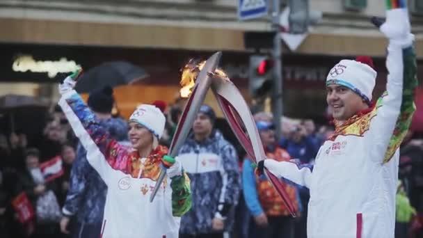 Petrohrad, Rusko - 27 října 2013: štafeta Soči olympijské pochodně v Petrohradu. Muž, Žena průvodců mávnout rukou. Předat plamen