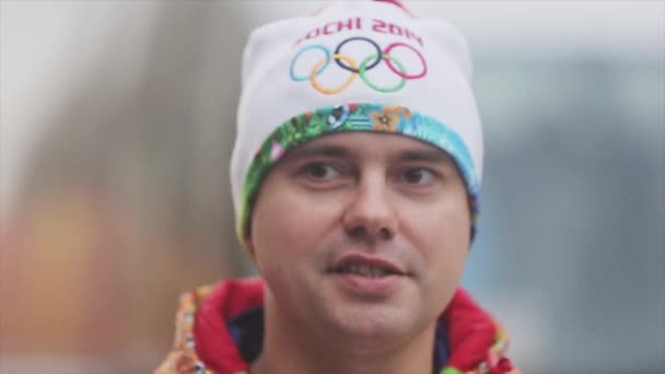 SAINT PETERSBURG, RUSSIA - OCTOBER 27, 2013: Relay race Olympic flame in Saint Petersburg. Portrait of adult male torchbearer give interview.