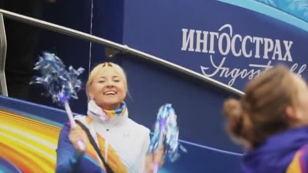 SAINT PETERSBURG, RUSSIA - OCTOBER 27, 2013: Volunteers shaking pom pom, dance. Bus. Relay race of Sochi Olympic flame in Saint Petersburg