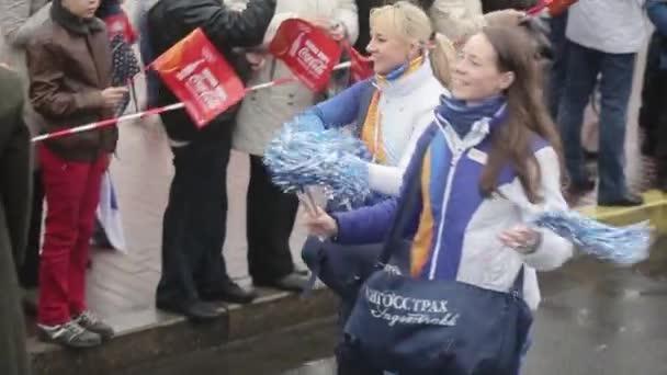 SAINT PETERSBURG, RUSSIA - OCTOBER 27, 2013: Happy volunteers give pom pom to people. Relay race of Sochi Olympic flame in Saint Petersburg.