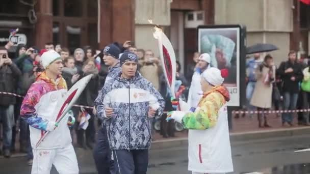 SAINT PETERSBURG, RUSSIA - OCTOBER 27, 2013: Relay race Sochi Olympic torch in Saint Petersburg. Aged female pass flame to man. Torchbearers