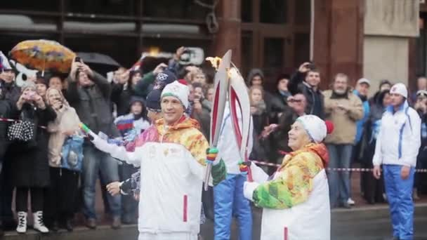 SAINT PETERSBURG, RUSSIA - OCTOBER 27, 2013: Relay race Sochi Olympic torch in Saint Petersburg. Aged female torchbearer pass flame to man. Smile