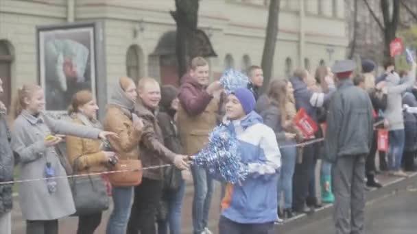 SAINT PETERSBURG, RUSSIA - OCTOBER 27, 2013: Boy volunteer run, give out pom pom people. Relay race of Sochi Olympic flame in Saint Petersburg