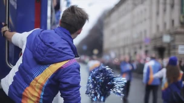 SAINT PETERSBURG, RUSSIA - OCTOBER 27, 2013: Boy shake pom pom stay at edge of driving bus. Relay race of Sochi Olympic flame in Saint Petersburg