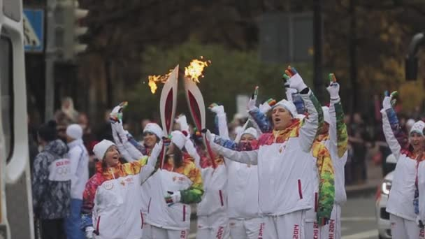 SAINT PETERSBURG, RUSSIA - OCTOBER 27, 2013: Relay race Sochi Olympic torch in Saint Petersburg. Team of torchbearers wave hands. Passing flame