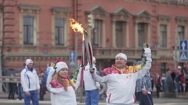SAINT PETERSBURG, RUSSIA - OCTOBER 27, 2013: Relay race Sochi Olympic torch in Saint Petersburg. Two torchbearers hold flame, wave hands.