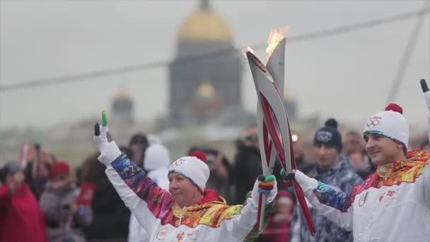 Petrohrad, Rusko-27. října 2013: závod ve společnosti Sochi olympijská pochodeň v Petrohradě. Dva z nich drží plamennou ruku lidem