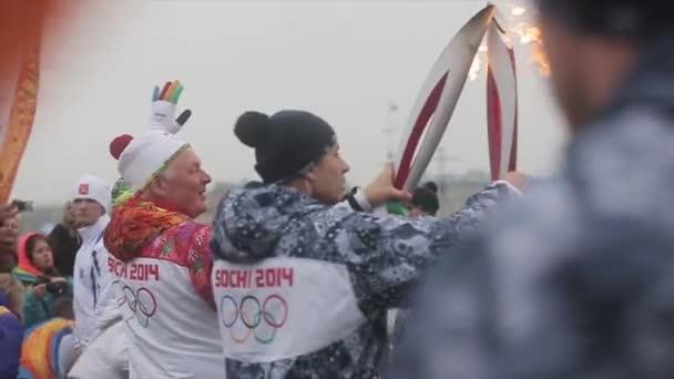 Petrohrad, Rusko-27. října 2013: závod ve společnosti Sochi olympijská pochodeň v Petrohradě. Zadní strany pochodů procházejí plamenem na nábřeží